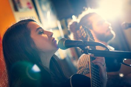 Dúo de guitarristas cantando durante una actuación musical. Luz de fondo con destello.