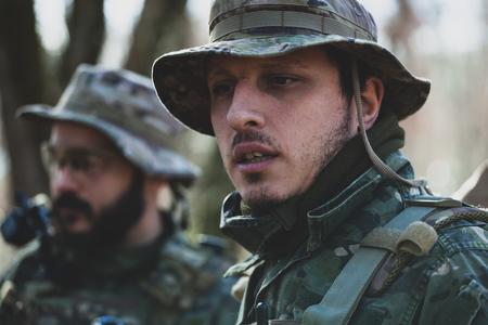 Jugadores de juegos militares de Airsoft en uniforme de camuflaje con rifle de asalto armado.