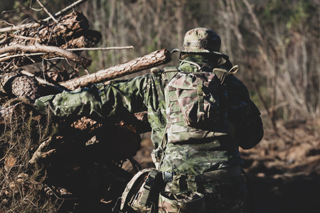 Airsoft military game player in camouflage uniform with armed assault rifle.