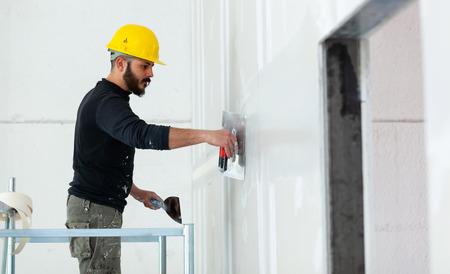 Construction intérieure, ouvrier plâtrant le mur de plaques de plâtre.