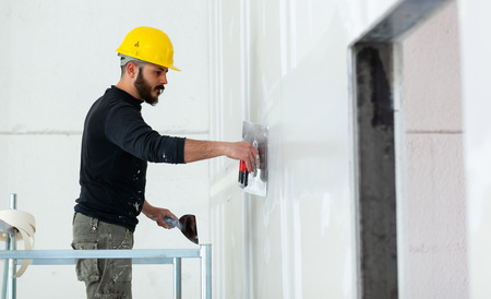 Interior construction, worker plastering gypsum board wall. Stockfoto