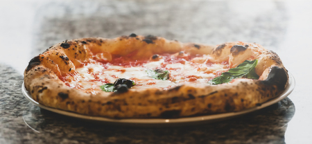 Selective focus of margherita pizza in plate on marble top.