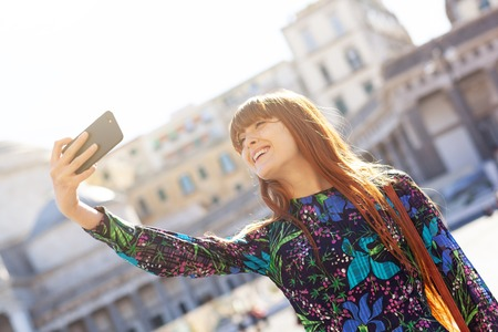 Beautiful young woman with red hair and freckles takes a selfie in Piazza Pebliscito in Naples.