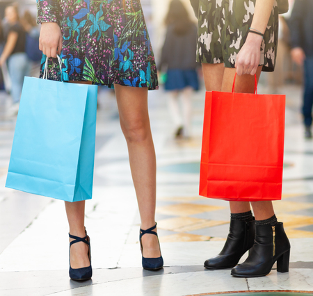 Closeup of legs and shopping bags of two young adults.