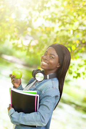 Portrait of a smiling african american female student holding a green apple.