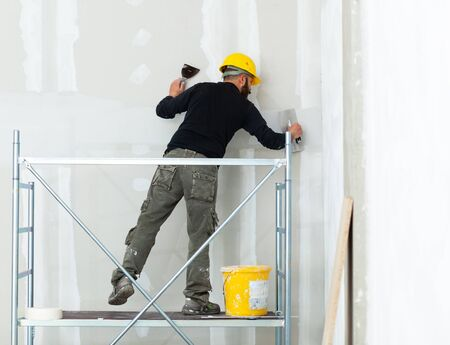 Interior construction, worker plastering gypsum board wall. Stockfoto