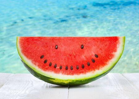 Sandía con semillas de smiley. Fondo con mar cristalino, concepto de comida de verano. Foto de archivo