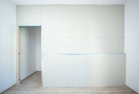 Wall made of plasterboard and prepared for painting for a wardrobe in a residential house. Фото со стока