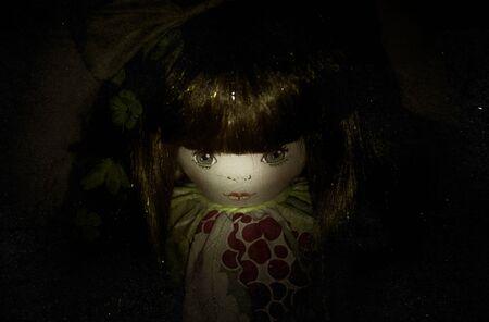Creepy doll in the dark. Horror concept.