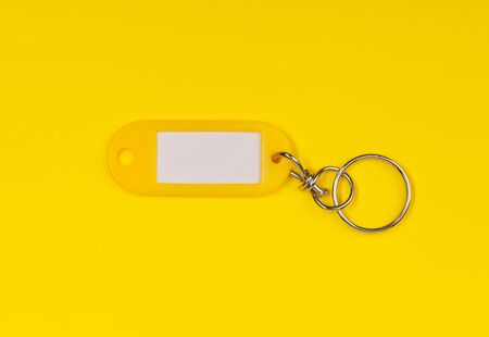 Vintage looking yellow key ring with blank paper label with copy space