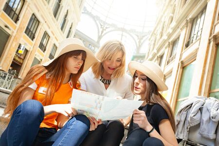 Three tourists consult the map of the city during their vacation.