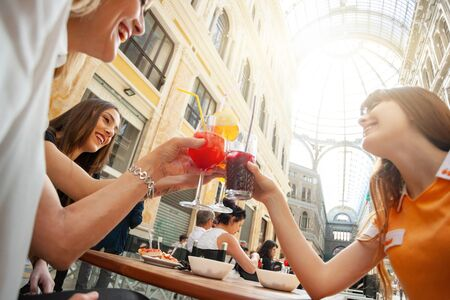 Friends do cheers with drinks in the gallery Umberto Primo in Naples. Stok Fotoğraf