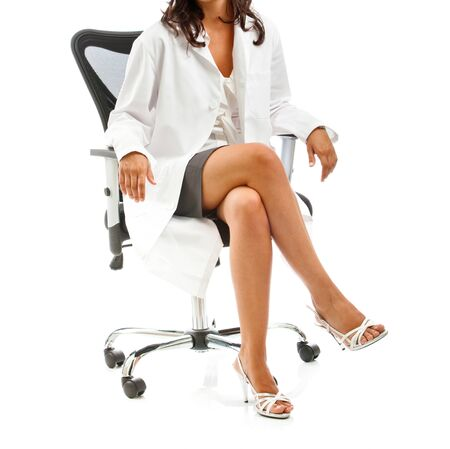 Female doctor sitting with crossed legs on office chair.