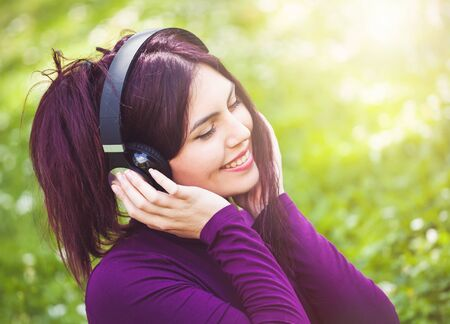Portrait of cute young woman listening music with headphones in outdoor.