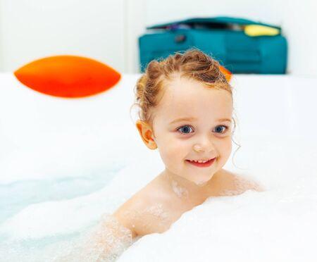 Happy little girl takes a bath in a hydromassage bathtub with foam.