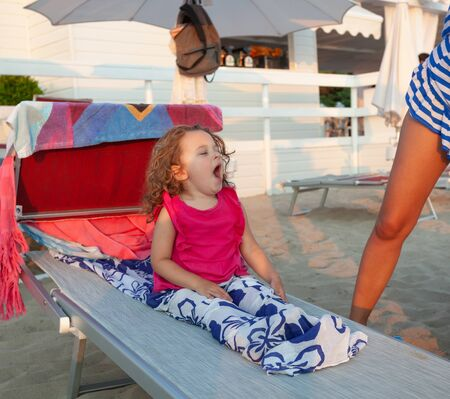 Adorable little girl yawns after a nap on the beach bed. Relax concept.
