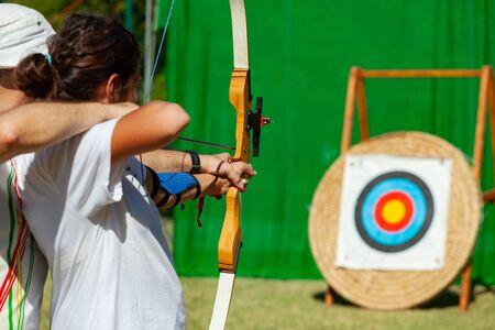 Archery course. The teacher teaches the student to aim at the goal.