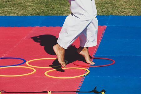 Martial arts teacher demonstrates to children how to jump in circles. Coordination exercise and equilibrium. Reklamní fotografie - 130795353