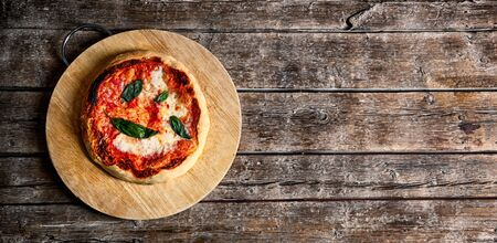Fresh Homemade Italian Pizza Margherita with basil on rustic background.