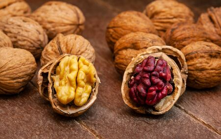 Red Danube and Juglans regia walnuts on wooden background, comparison concept. It originated from a cross between English and Persian walnut trees