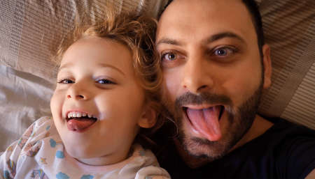 Authentic close up of a dad and daughter making funny faces, looking at the screen for a selfie, in a bed. Concept of family and emotional relationship between daughter and father.