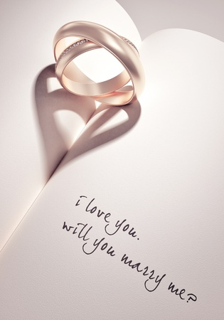 will you marry me: heartshadow with rings on a book middle - i love you - will you marry me - card Stock Photo