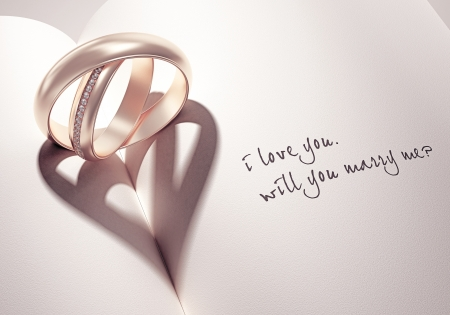 ring wedding: heartshadow with rings on a book middle - i love you - will you marry me - card Stock Photo