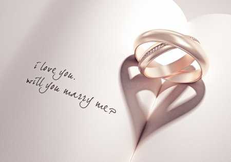 heartshadow with rings on a book middle - i love you - will you marry me - card Stock Photo