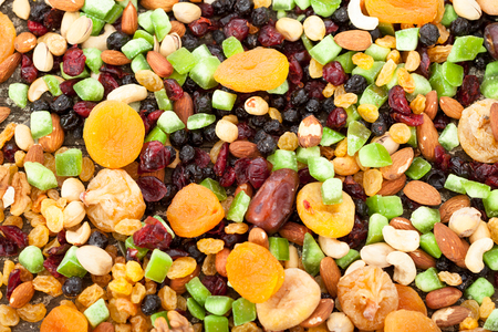 Background of mixed dried fruits (raisins, apricots, figs, prunes, goji, cranberries, blueberries, prunes) and nuts (almonds, hazelnuts, peanuts, cashews) Stock Photo