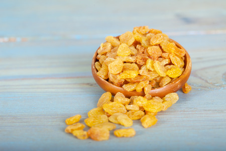Golden raisins or dried grapes in wooden bowl, blue background