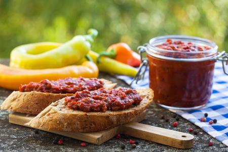 Ajvar - leckeres Gericht mit gerösteten Paprika auf Brot verteilen