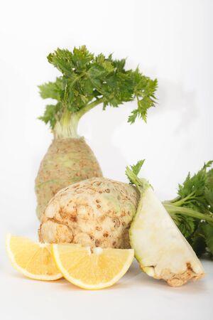 Fresh celery root vegetable with slice of lemon, white background, vertical