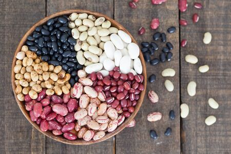 lima beans white beans: Assortment of different types of beans - red beans, chickpeas, peas in wooden bowl. top view.
