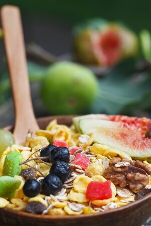 Healthy breakfast. Muesli in bowl with fresh figs, berries, seeds and nuts on vintage wooden background, vertical