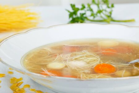 carot: Chicken soup with noodles and vegetables in white plate
