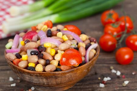 Salad made of beans, chickpeas and corn with spring onions and cherry tomatoes. Wooden background.