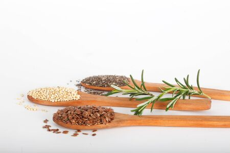 linseed: Healthy grains including flax seed, white grain quinoa and chia seed in wooden spoons Stock Photo
