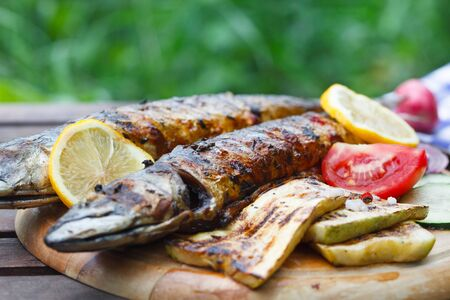 Grilled mackerel fish with lemon and vegetables on wooden board.