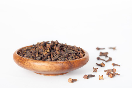 Cloves in wooden bowl on white background. Cloves have anti-carcinogenic properties.