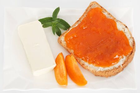 marmelade: Slice of bread with butter and apricot marmelade.