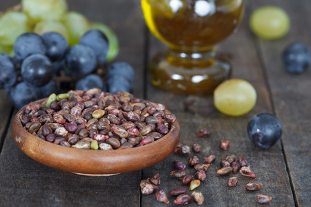 Grape seed in wooden bowl. Antioxidant, healthy grape seed oil and fresh grape on the table. Closeup view. Banque d'images
