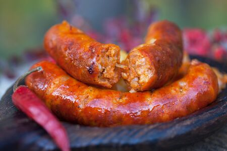 Grilled sausages with potatoes on wooden plate, outdoor image, closeup Stock Photo