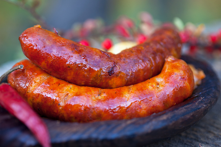 Homemade Hot Sausages. Grilled sausage on dark wooden plate