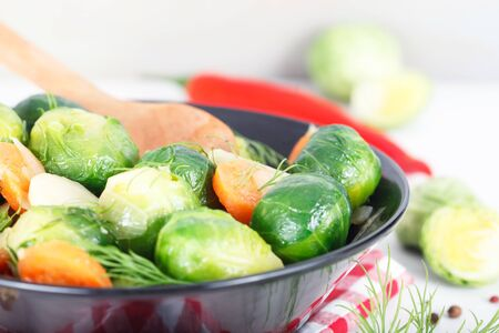 Homemade cooked Brussel Sprouts with salt, pepper and onions in black bowl