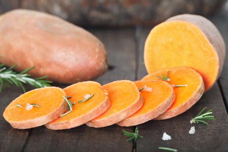 Raw sweet potatoes on wooden background closeup Standard-Bild