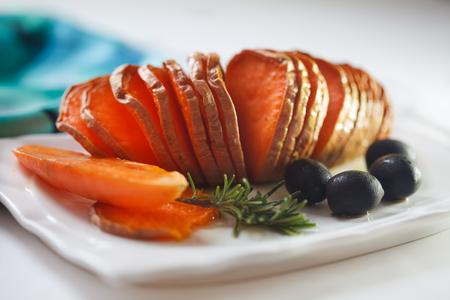 Homemade Orange Sweet Potato with olives and rosemary. Hassel back potato. Stock Photo