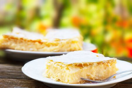 Traditional Polish Cream Pie filled with yellow pudding cream.Karpatka. Stock Photo