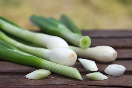 Fresh healthy spring onions on wooden table, outdoor image.Choped green onions.