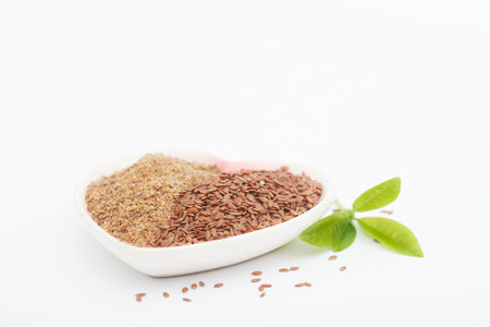 Whole and ground or crushed brown flax seed or linseed with grinder on white background. Healthy food for preventing heart diseases and overweight.