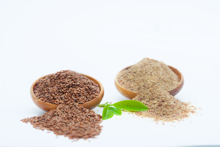 Flax seeds and grinded  linseed in wooden bowls. Healthy food for preventing heart diseases and overweight. Zdjęcie Seryjne